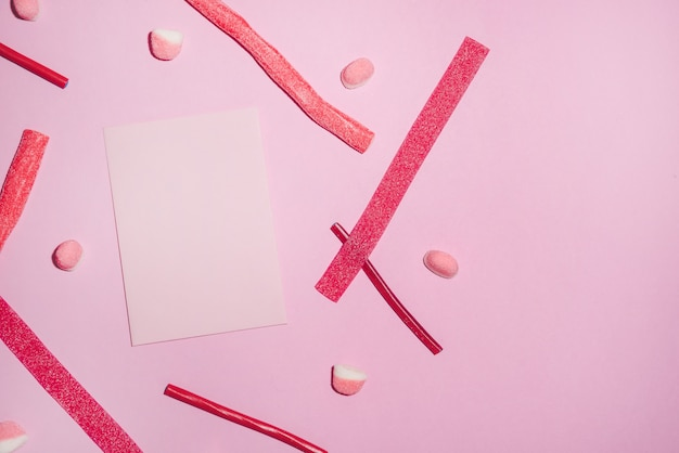 Rote zuckersüßigkeiten und lollies mit leerem blatt papier