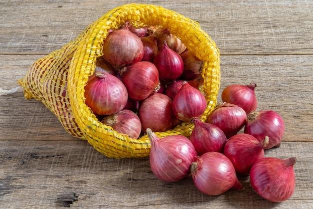 Rote zwiebel auf schäbigem holzbrett.