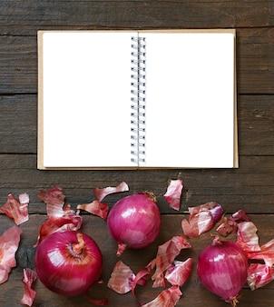 Rote zwiebeln auf einem holztisch mit notizbuch-draufsicht