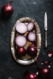 Rote zwiebeln der draufsicht auf einer platte und einem messer