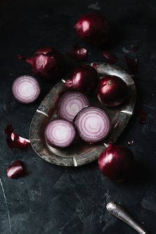 Rote zwiebeln der hohen ansicht auf einer platte und einem messer