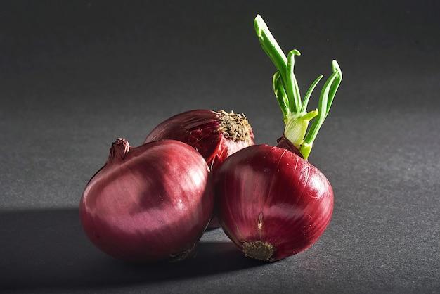 Rote zwiebeln ganz, isoliert auf einem schwarzen