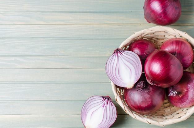 Rote zwiebeln in einem weidenkorb. frische ernte. heller holzhintergrund. flache draufsicht. speicherplatz kopieren