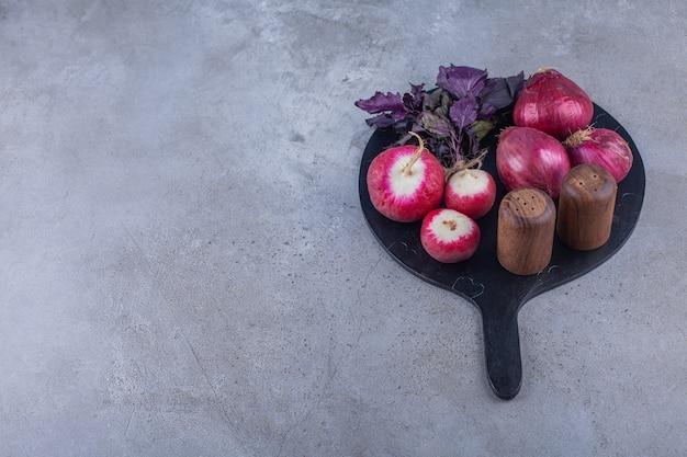 Rote zwiebeln, radieschen und frisches basilikum auf schwarzem schneidebrett.