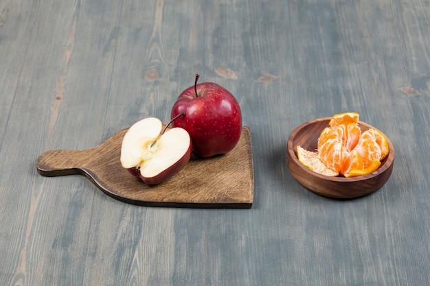 Roter apfel auf holzbrett mit schüssel mit mandarinensegmenten