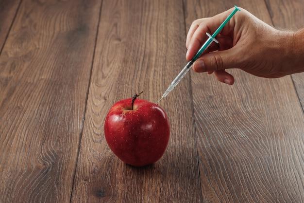 Roter apfel, der eine nadel oder eine spritze und chemische schädlingsbekämpfungsmittel auf einem hölzernen hintergrund einspritzt
