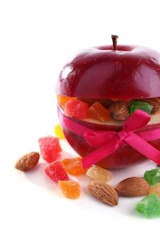 Roter apfel gefüllt mit getrockneten früchten mit zimt und mandeln isoliert auf weiß