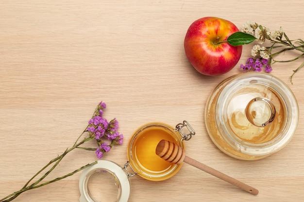 Roter apfel, granatapfel und honigglas für jüdisches neues jahr auf hölzernem brett