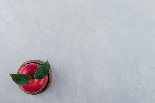 Roter apfel mit blättern in holzschale