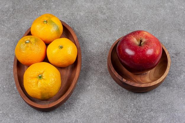 Roter apfel mit süßen mandarinen auf einem holzbrett