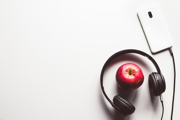Roter apfel mit telefon, kopfhörer auf weißer oberfläche