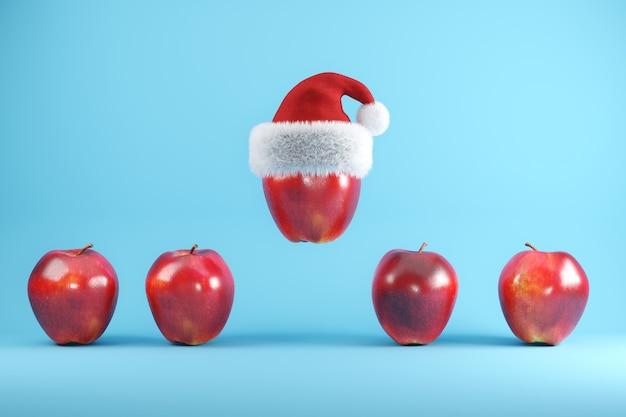 Roter apfel mit weihnachtsmütze schwimmt auf blau