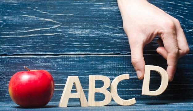 Roter apfel und buchstaben abcd. die hand setzt den buchstaben d in alphabetischer reihenfolge