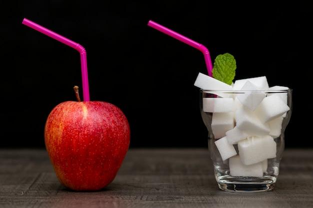 Roter apfel und cocktail mit zuckerwürfeln, wahl des zuckerkonsums