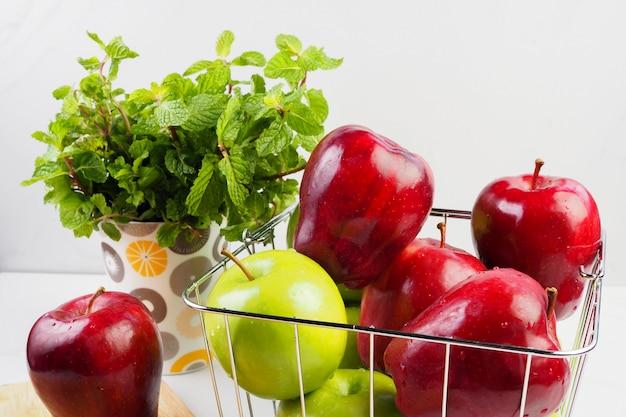 Roter apfel und grüner apfel im korb auf weißer tabelle