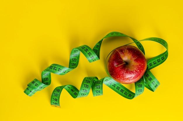 Roter apfel und grünes messendes band auf gelb