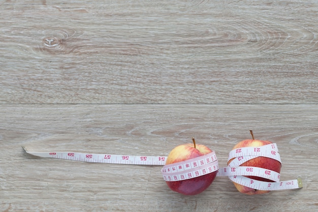 Roter apfelkern und maßband. konzept der gewichtskontrolle abnehmen mit obst, diät-konzept, nebenwirkungen von übermäßigem gewichtsverlust.