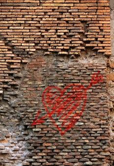 Roter backsteinwandbeschaffenheit-schmutz-hintergrund mit herzgraffiti