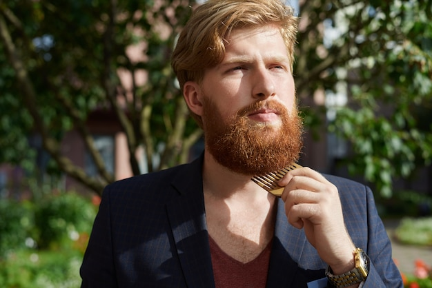 Roter bärtiger hipster im sommer zu fuß und kämmt seinen bart aus