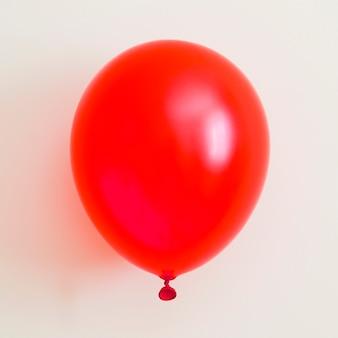 Roter ballon auf weißem hintergrund