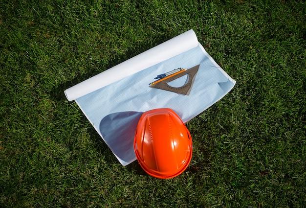 Roter bauarbeiterhelm, der am sonnigen tag auf blaupause auf gras liegt