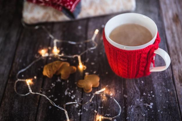 Roter becher des weihnachtskaffees oder -tees mit dampf, selbst gemachte lebkuchenweihnachtsplätzchen auf holz