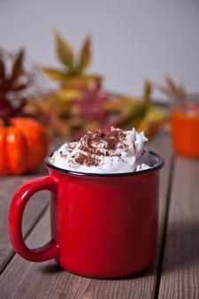 Roter becher heißer sahniger kakao mit schaum auf hölzerner tabelle mit herbstlaub, kerze und kürbis