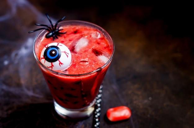 Roter beerencocktail mit eis, augen und spinnen für halloween-party mit netz
