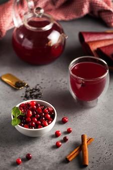 Roter beerentee ihrer preiselbeeren, schwarzer tee, zimt, ingwer und minze in einer teekanne mit einem becher und einer schüssel preiselbeeren
