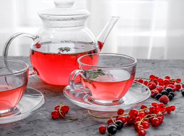 Roter beerentee in der schale und in der teekanne