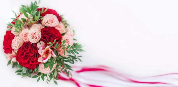 Roter blumenstrauß auf weißem hintergrund. banner zum valentinstag, hochzeit. hochzeitsstrauß mit rosen und nelken