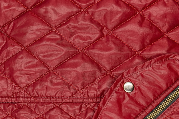 Roter bologna-stoff mit aufgenähten rauten und tasche mit knopf und reißverschluss.