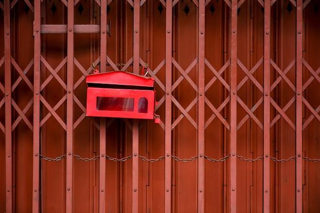 Roter briefkasten an der metallschiebetür