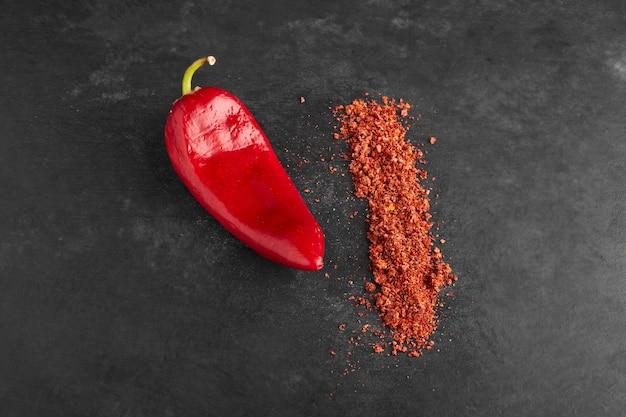 Roter chili mit paprika auf schwarzer oberfläche.