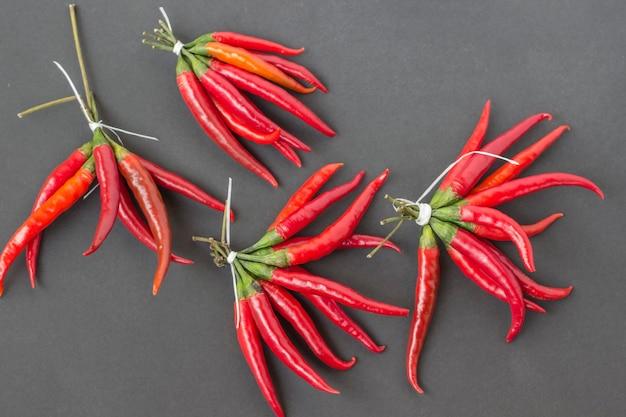 Roter chili-pfeffer gebunden in bündeln auf einem schwarzen tisch