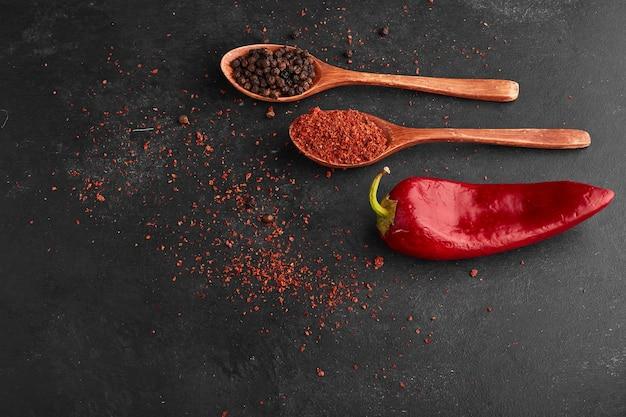 Roter chili-pfeffer mit paprika in einem holzlöffel.