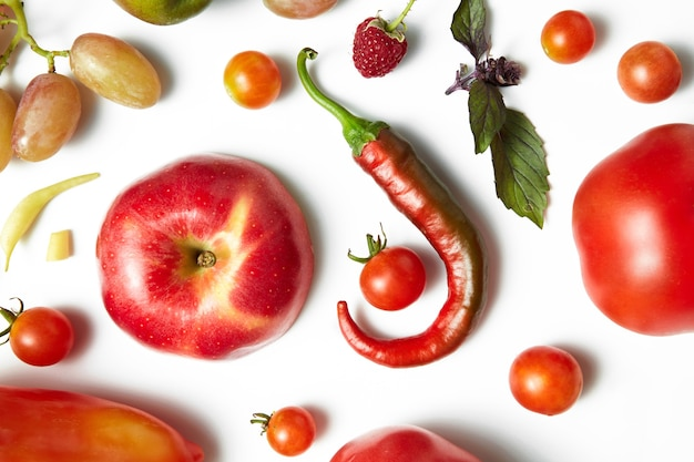 Roter chili-pfeffer und tomate auf weißem tisch. gesundes essen und essen für veganer