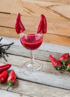 Roter cocktail für halloween-feier mit teufelshörnern chilischoten verziert. auf holzoberfläche