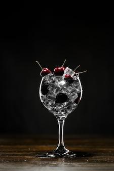 Roter cocktail in einem glas mit eis und kirschen