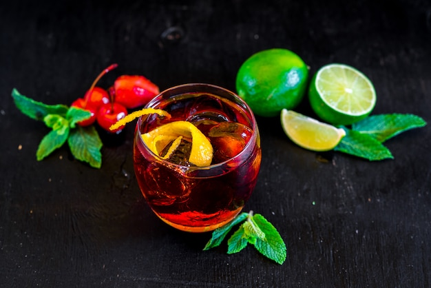 Roter cocktail mit eis und orange auf schwarzem hintergrund