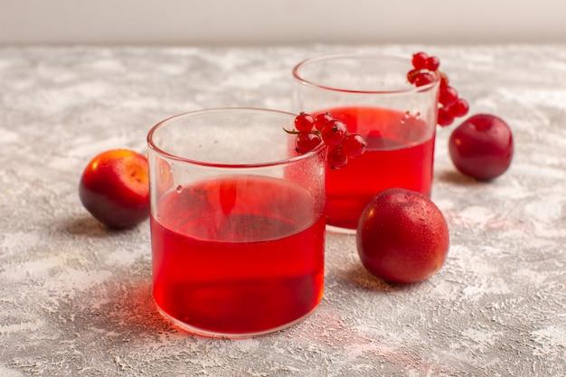 Roter cranberrysaft der vorderansicht mit frischen pflaumen