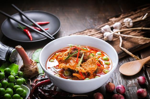 Roter curry mit schweinefleisch und kokosmilch, köstliches thailändisches lebensmittel auf holztisch.