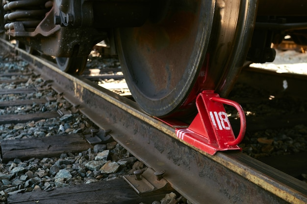 Roter eisenbahnbremsschuh unter dem rollenden material befestigt.