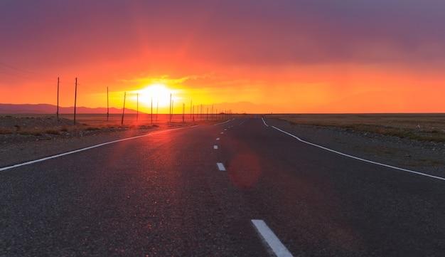 Roter erstaunlicher sonnenuntergang über einer unendlich langen asphaltstraße in der altai-republik