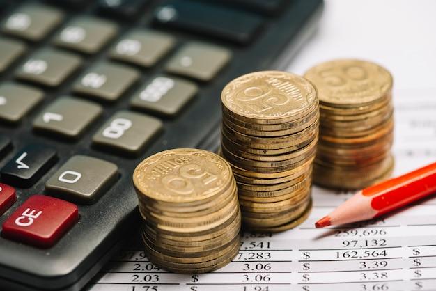 Roter farbiger bleistift mit taschenrechner und stapel münzen über dem finanzbericht
