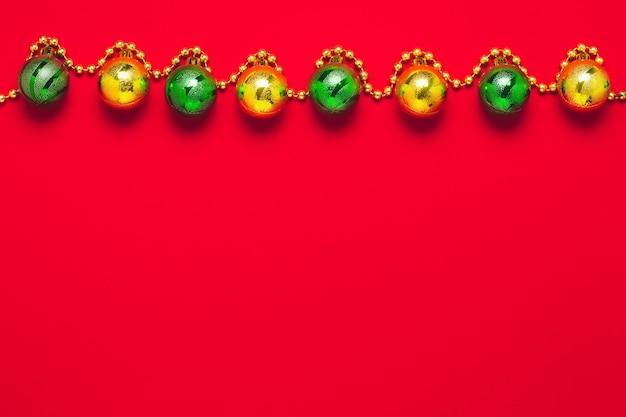 Roter festlicher hintergrund mit gold- und grünkugeln.