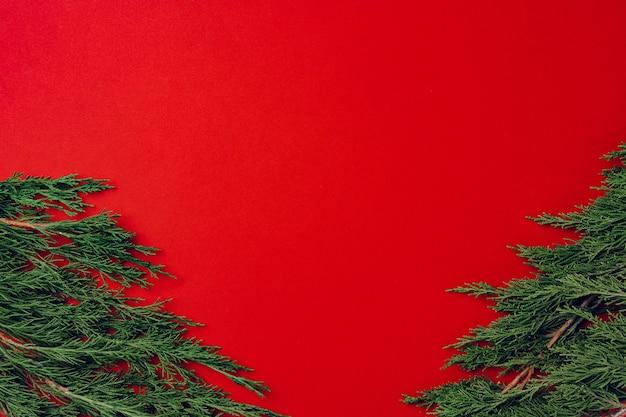 Roter festlicher weihnachtshintergrund mit nadelzweigen, kopienraum