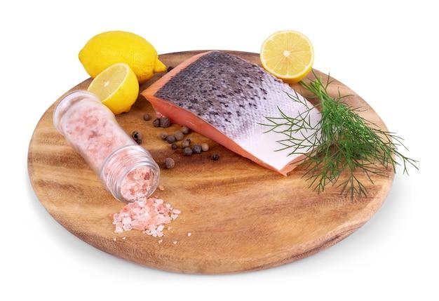 Roter fisch mit zitrone, pfeffer und petersilie isoliert auf weißem hintergrund