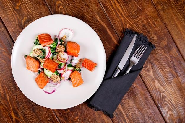 Roter fischlachs mit rettich und spinat, serviert auf weißem teller auf holztisch. rustikaler stil. ansicht von oben, obere studioaufnahme