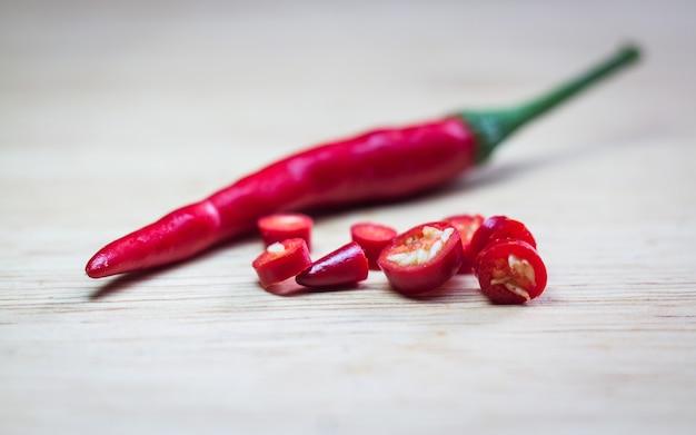 Roter frischer chili auf altem rustikalem holzschreibtisch. lebensmittel hintergrund. kochen. selektiver fokus